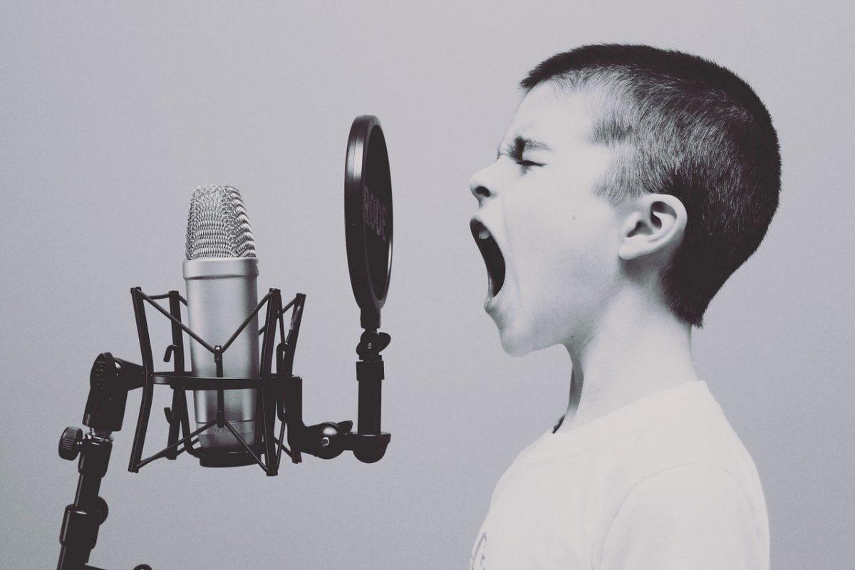 niño grita frente un micrófono